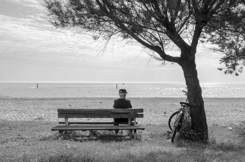 Man sitting on bench by beach