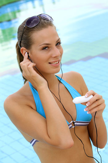 young blond woman listening to music with MP3 players at the pool Beautiful Happy Holiday Listening Music Music Summer Holidays Woman Beautiful Woman Beauty Bikini Blond Girl Happyness Leisure Leisure Activity Lifestyles Mp3 Player One Person Pretty Relaxation Swimming Pool Vacation Water Wellbeing Young Women