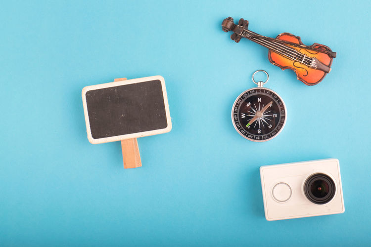 flat lay traveler accessories on blue background Still Life Indoors  No People Blue Studio Shot Copy Space Technology Directly Above High Angle View Colored Background Table Music Shape Close-up Geometric Shape Blue Background Arts Culture And Entertainment Metal Group Of Objects