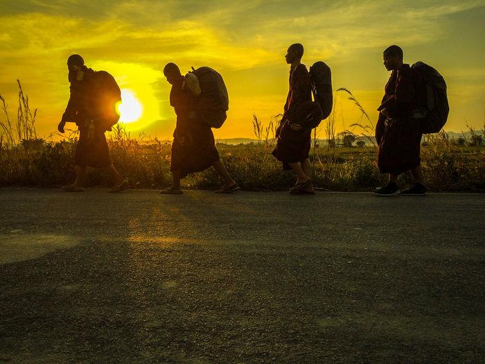 Men standing against sky during sunset