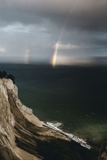 Scenic view of sea against rainbow in sky