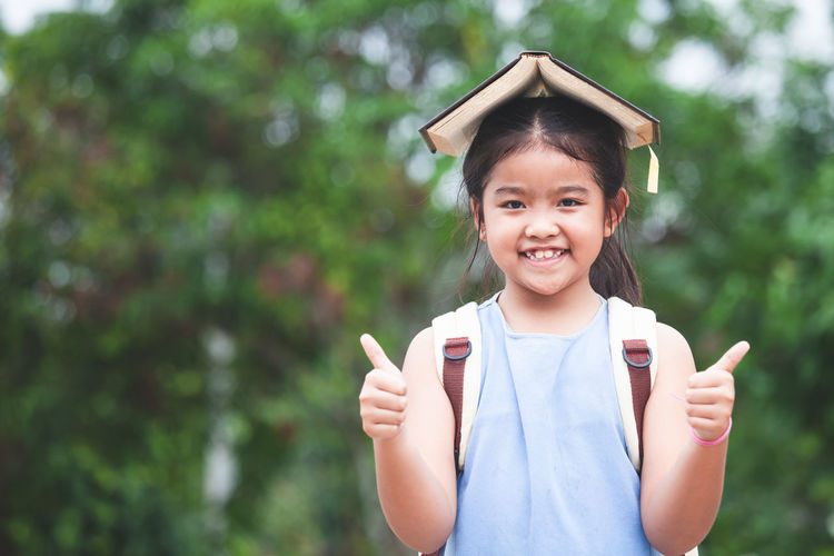 Back to school. Cute asian child girl with school bag put a book on head and love to go to school Asian  Happy Student Adorable Assessories Back To School Backpack Bag Book Child Cute Girl Holding Kid Knowledge Learn Magnifying Glass Portrait Pupil School Smiling Study