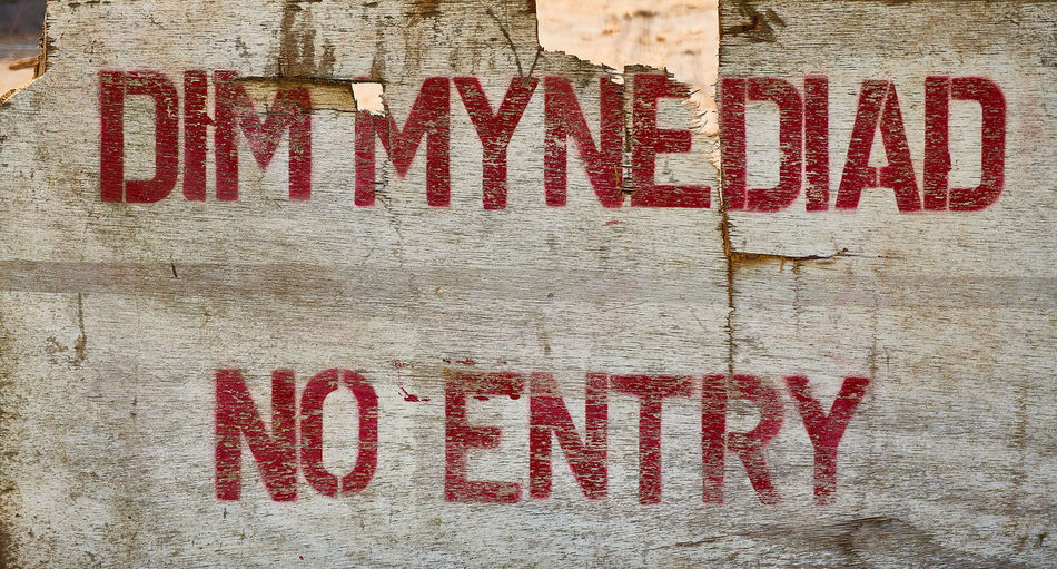 No entry sign in english and Welsh No Entry Welsh Backgrounds Capital Letter Close-up Communication Creativity Full Frame Indoors  Information Message No People Non-western Script Red Script Sign Text Textured  Wall - Building Feature Welsh Language Western Script White Color Wood - Material