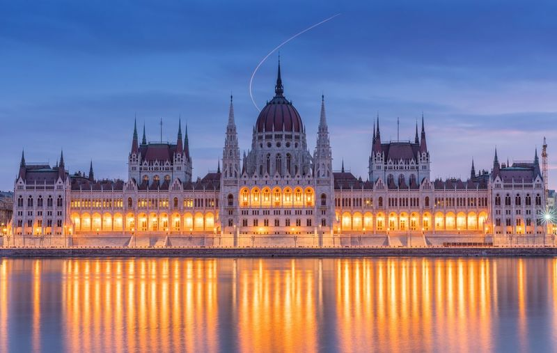 Hungarian Parliament Building By River In City At Dusk
