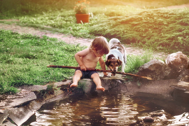 Full length of shirtless boy holding stick sitting by pond with dog