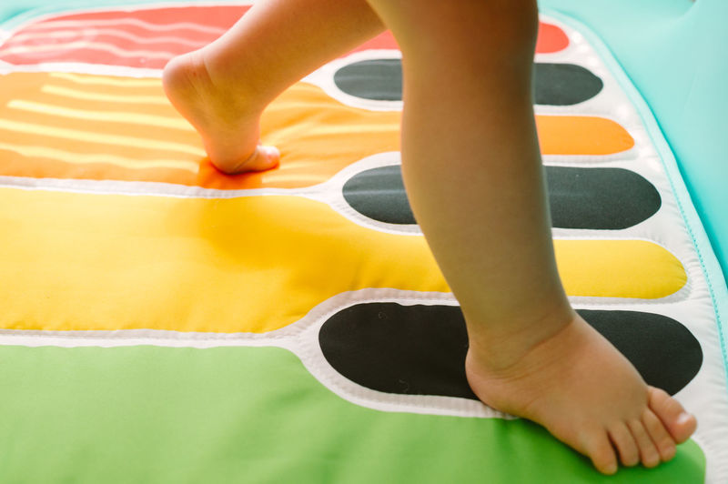 Low Section Of Baby Boy Walking On Piano Designed Mat