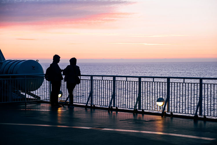 Silhouette men standing on railing by sea against sky during sunset