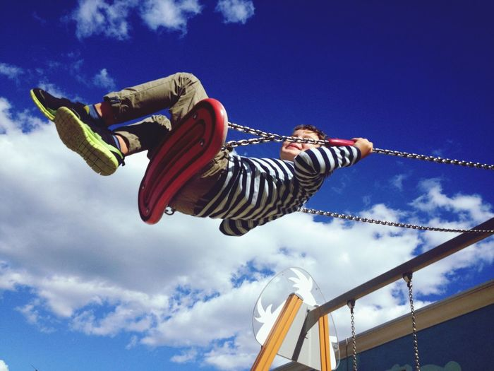 Low angle view of boy swinging against blue sky at playground