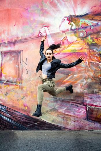 Portrait of woman jumping against graffiti wall