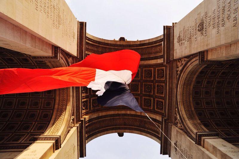 Directly below shot of french flag waving below arc de triomphe