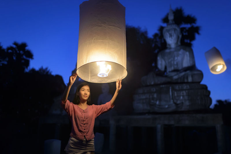 Low angle view of woman holding lit paper lantern at night