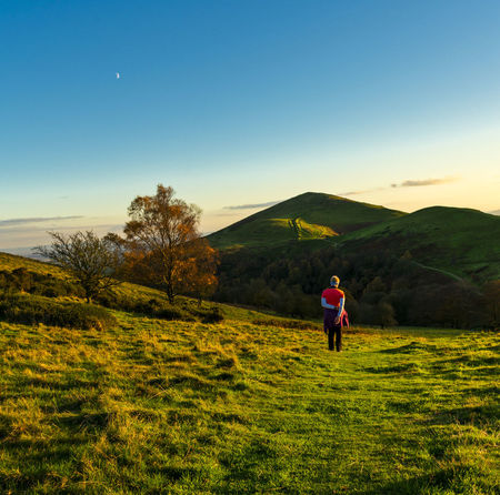 A woman walking in contemplation on the Malvern Hills, Malvern, UK Contemplation Malvern Hills Quiet Moments Woman Blue Sky Landscape Moon Light One Person Peaceful Walking