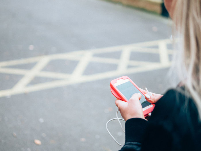 Woman using mobile phone on road