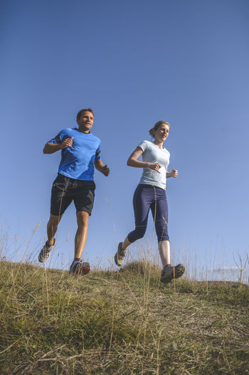 Personal Training Personal Training Running Woman Clear Sky Day Fitness Fitness Training Full Length Jogging Leisure Activity Lifestyles Low Angle View Men Nature Outdoors Personal Trainer Sport Sports Clothing Together Togetherness Two People