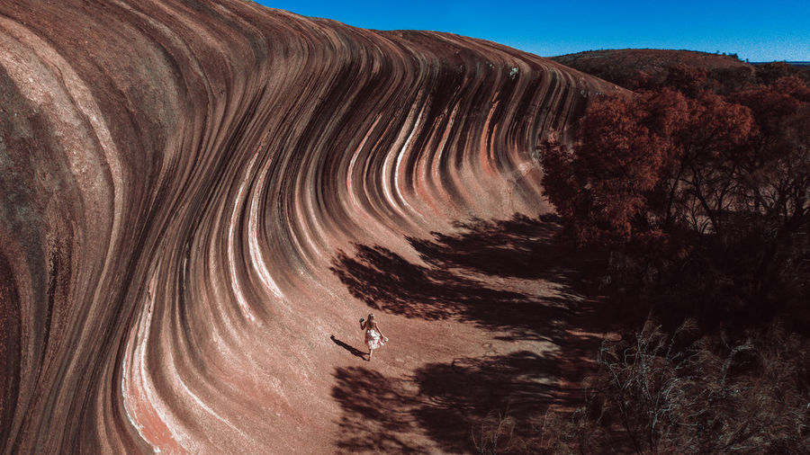 High angel view of woman walking by rock formation against sky