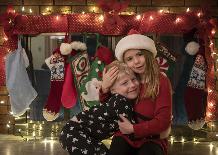 A brother gets a hug from his big sister in a Santa hat in front of a fireplace with Christmas decorations in their home. Hat Women Clothing Females Christmas Togetherness Happiness Winter Emotion Smiling Celebration Two People Fun Bonding Positive Emotion Holiday Leisure Activity Illuminated Warm Clothing Santa Hat Lights Love Siblings Hug Stockings Holiday Moments