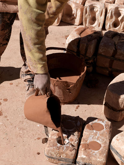Low section of man making pottery in workshop