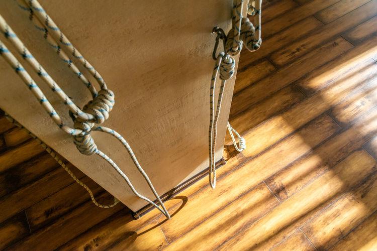 High angle view of rope on hardwood floor