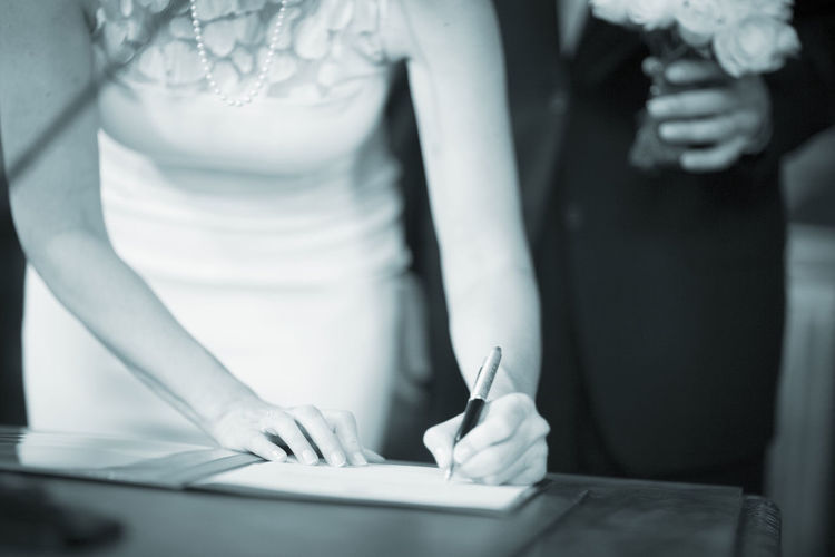Midsection of bride signing with groom holding flower bouquet in background