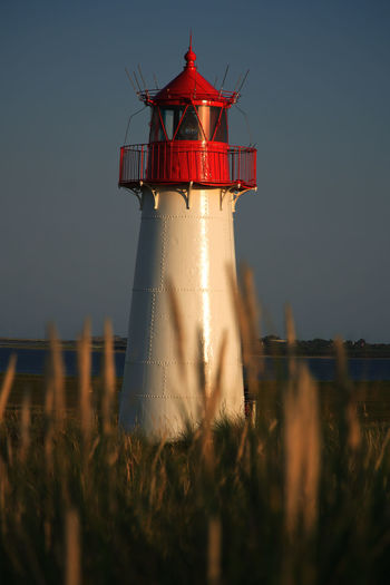 Red and white lighthouse at sky during sunset