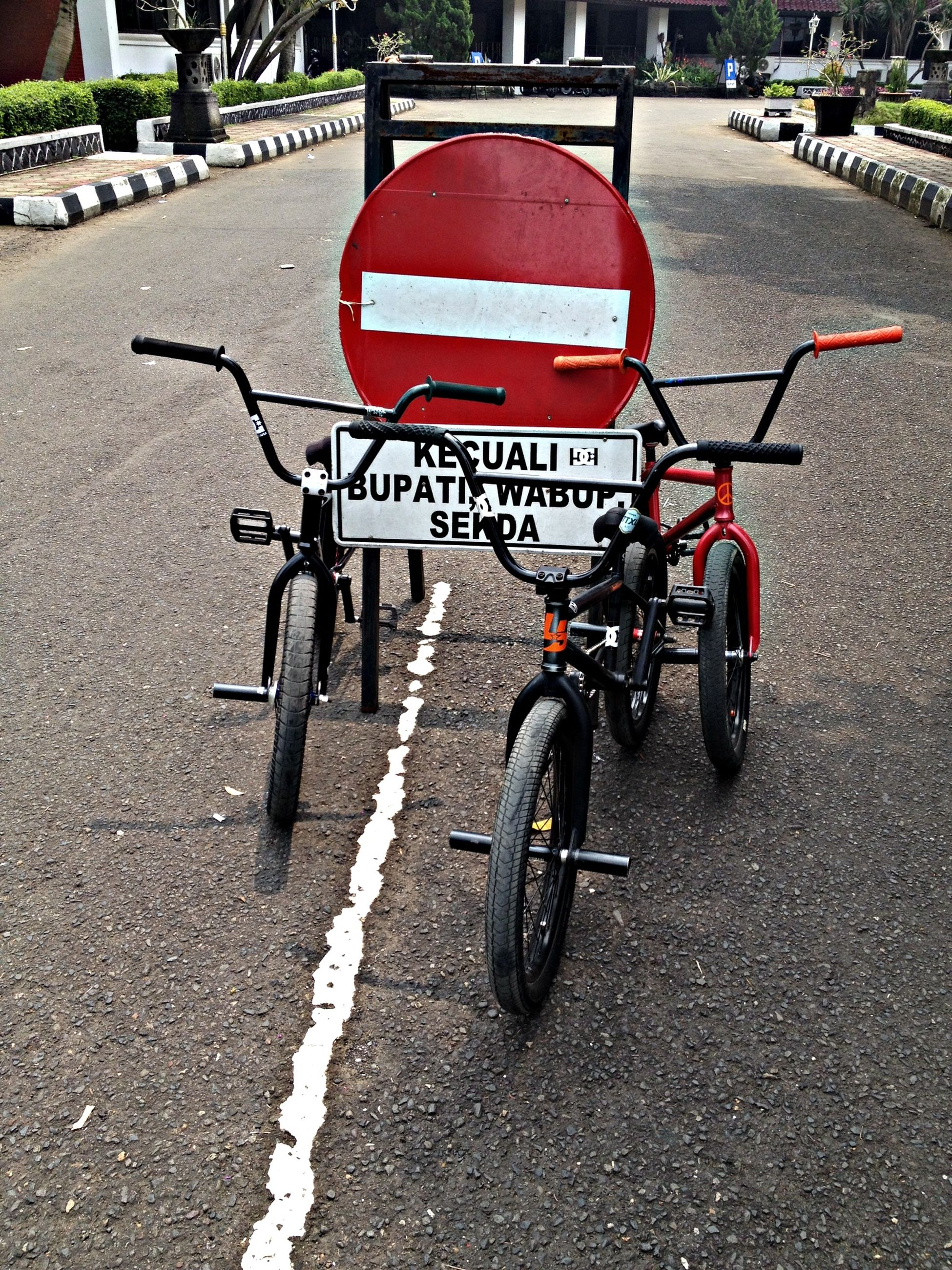 transportation, mode of transport, land vehicle, bicycle, street, road, road marking, asphalt, car, stationary, parking, road sign, city, guidance, parked, motorcycle, day, the way forward, parking lot, outdoors