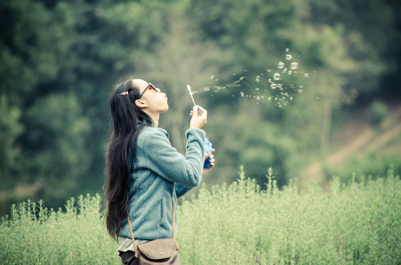 Side view of girl blowing bubbles while standing at park