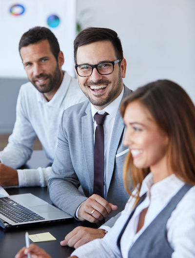 Portrait of smiling businessman with colleagues at office