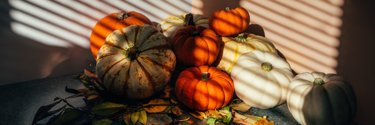 Happy thanksgiving text with background of pile of different pumpkins with strong shadows.