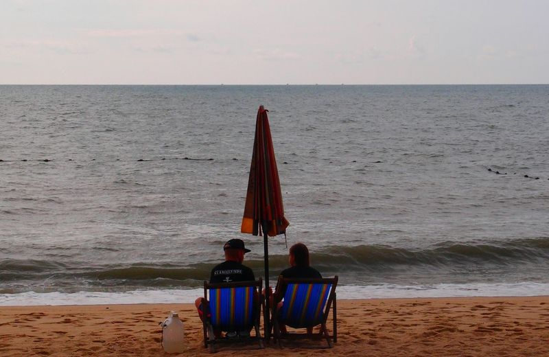 Rear view of lifeguards sitting on chair against sea at beach