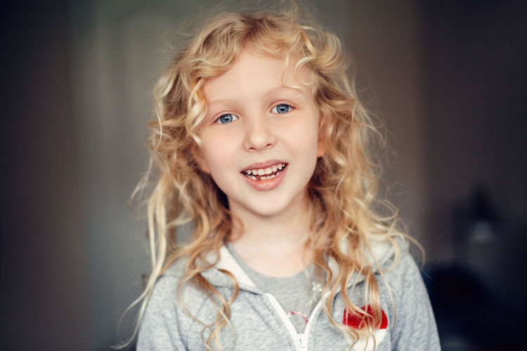 Portrait of smiling caucasian blonde girl with long messy hair. missing lost milk tooth.