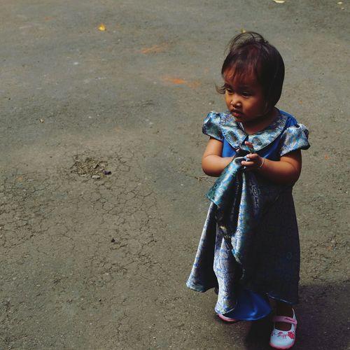Cute girl in blue dress standing on road