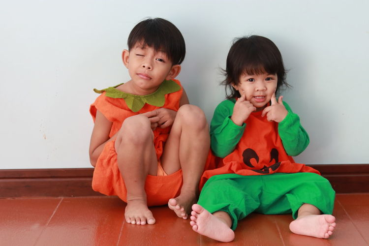 Portrait of cute kids sitting on floor at home