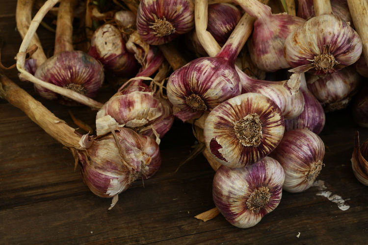 High Angle View Of Garlics On Wooden Table