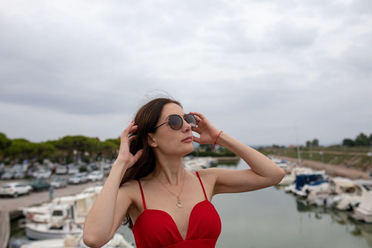 Woman wearing sunglasses while standing against boats moored at harbor
