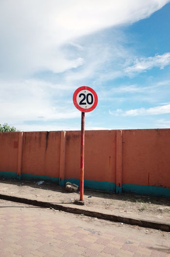 Speed limit sign on sidewalk against sky