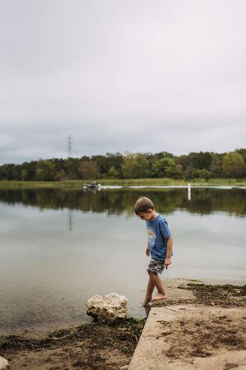 Full length of boy on lake against sky