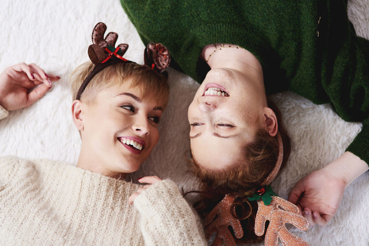High angle view of cheerful sisters wearing headbands while lying on rug