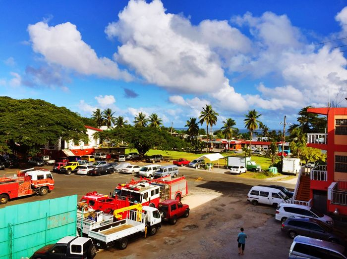 High angle view of land vehicles at parking lot against cloudy sky