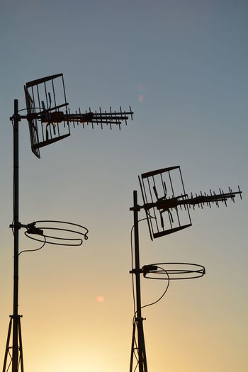 Low angle view of silhouette television aerials against sky during sunset