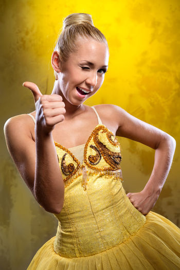 Portrait of beautiful ballerina showing thumbs up against yellow background