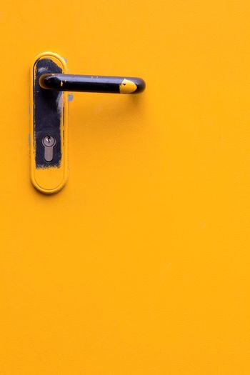 Full Frame Paint Painted Yellow Copy Space Metal No People Wall - Building Feature Single Object Colored Background Close-up Orange Color Simplicity Handle Safety Closed Latch Lock Hinge Keyhole Locked Security Safe Door Closed Door Orange Background Front Door Entryway Door Handle Backgrounds