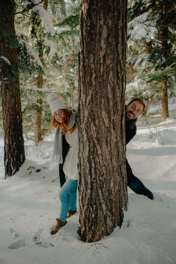 Portrait of couple standing by tree trunk during winter