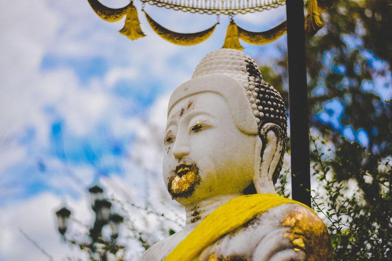 Close-up of buddha statue against sky