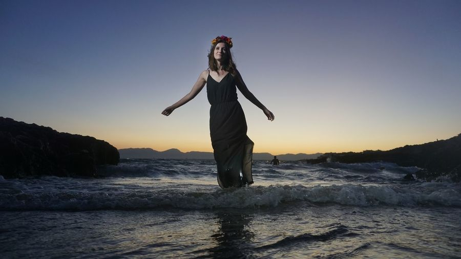 Full length of woman standing at beach during sunset