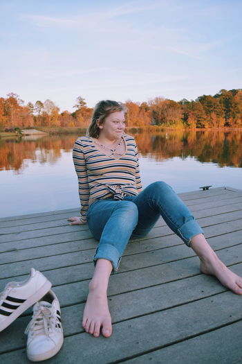 Full length of young woman sitting on lake against sky