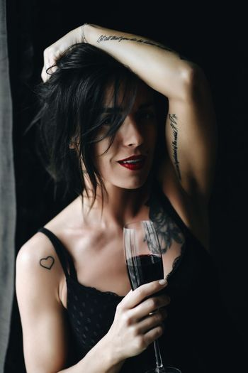 beautiful brunette girl millennial drinks red wine and have fun. One Person Indoors  Young Adult Women Portrait Front View Adult Young Women Beautiful Woman Holding Headshot Fashion Lifestyles Black Background Beauty Hair Real People Refreshment Hairstyle Glass