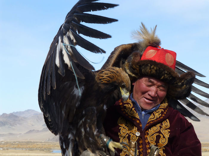 An eagle hunter, Western Mongolia. Altai Mountains Eagle Golden Eagle Festival Man Mongolia Ulgii Animal Wildlife Bird Clothing Day Festival Front View Lifestyles Nature One Person Outdoors Portrait Real People Sky Vertebrate Waist Up Warm Clothing