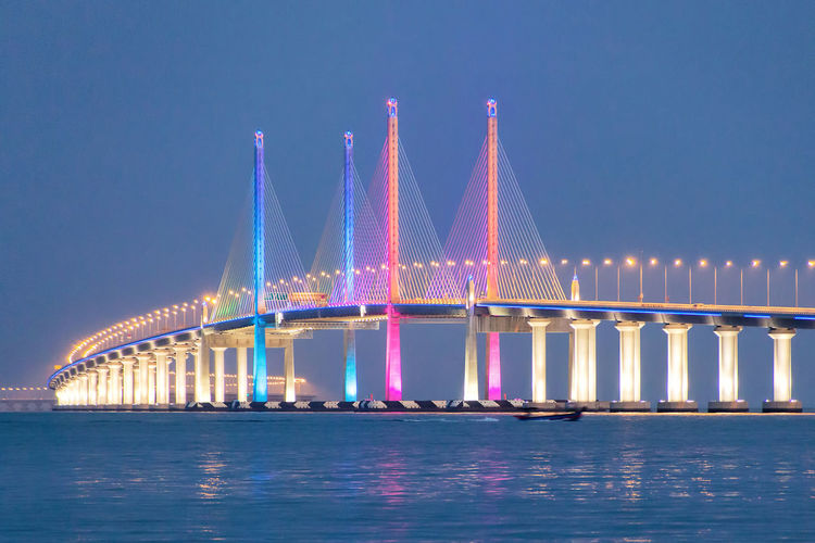 Illuminated colorful penang bridge over strait of malacca against clear sky at dusk