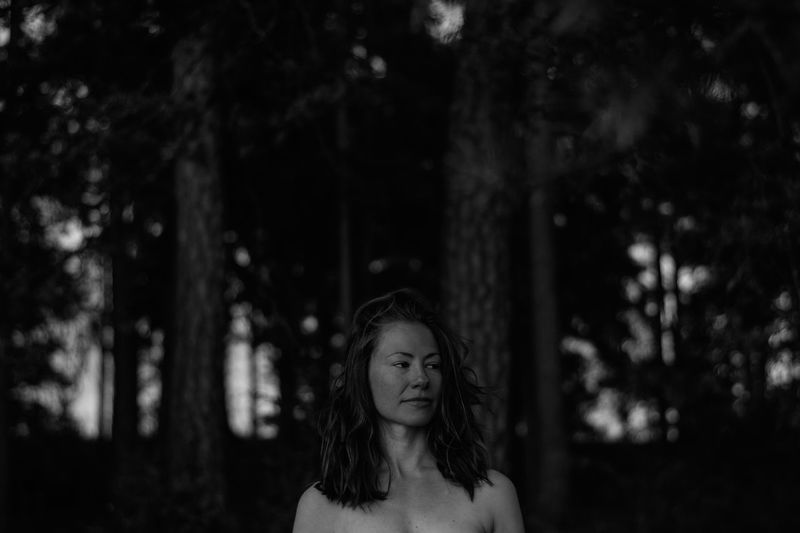 Thoughtful shirtless woman looking away while standing in forest at dusk