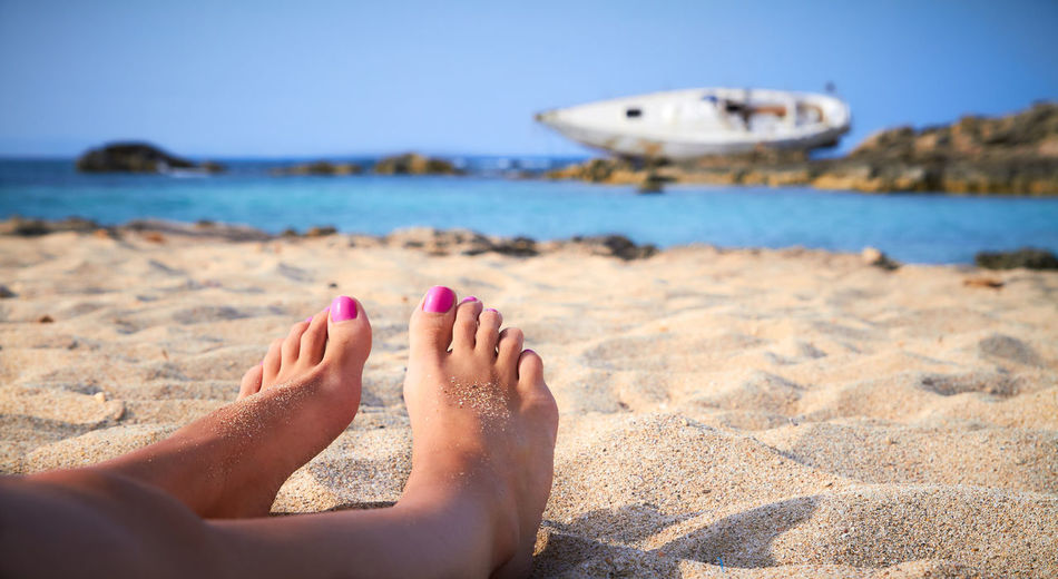 A girl sunbathes on a beach of Formentera in the Balearic Islands, Spain Adult Barefoot Beach Beach Holiday Blue Close-up Coastline Horizon Over Water Human Body Part Human Foot Nail Polish Nature Outdoors People Pink Color Red Relaxation Sand Sea Sky Summer Toenail Vacations Water Women